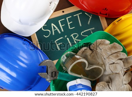 color helmets and board with the inscription SAFETY FIRST - stock photo
