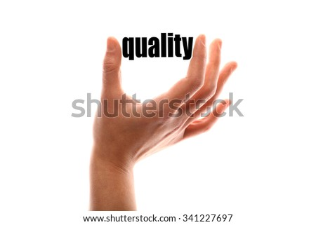 """Color horizontal shot of a of a hand squeezing the word """"quality"""". - stock photo"""