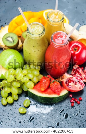 Color Juices Smoothie Bottles Red Green Orange Fruits Water Melon  Apple  Strawberry Kiwi Grapes Mango Pomegranate Tropical Selective Focus Black Background Healthy Beverage - stock photo