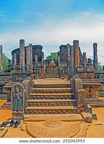 Color Paintings Meditating Buddha Statue in Ruined Pagoda at Ancient City of Anuradhapura, Sri Lanka on Sandstone Texture - stock photo
