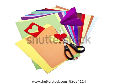 Color paper sheets with scissors and paper craft isolated on white - stock photo