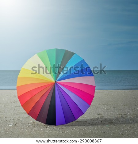 Color pattern of an umbrella with the sky as background. - stock photo