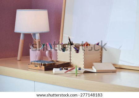 Color pencil and rubber stamp set with notebook on the wooden table for kids - stock photo