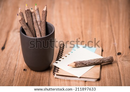 color pencil made of branches in cup and note book on wood background - stock photo