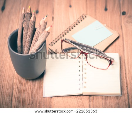 color pencil made of branches with glasses and note book on wood background,vintage tone style - stock photo