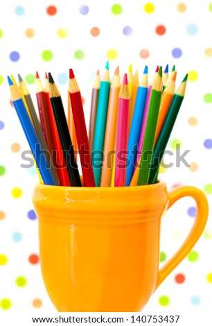 Color pencils in an orange cup with a polka dot background. Colorful image for back to school. - stock photo
