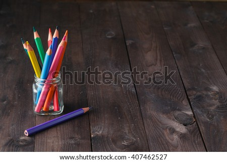 Color pencils in the stand holder on the wood vintage background copy space - stock photo
