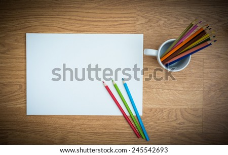 Color pencils in white coffee cup on white paper wooden background - stock photo