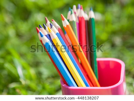 Color pencils into the pencil holder, natural green background - stock photo