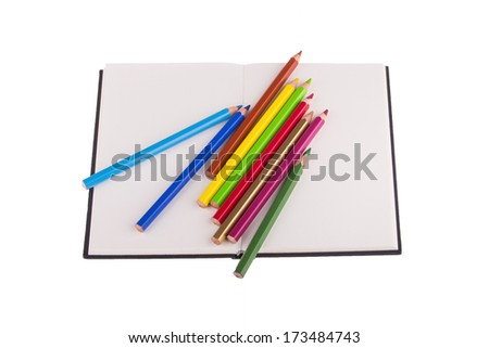 Color pencils placed on notebook, isolated on white background. - stock photo