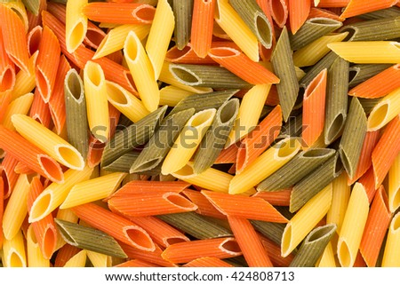 Color penne pasta. Tomato, spinach and wheat pastas in horizontal format - stock photo