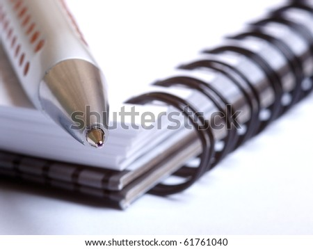 Color photo of a ballpoint pen and notebook - stock photo