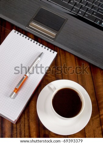 Color photo of a workplace with a laptop and a cup of coffee - stock photo
