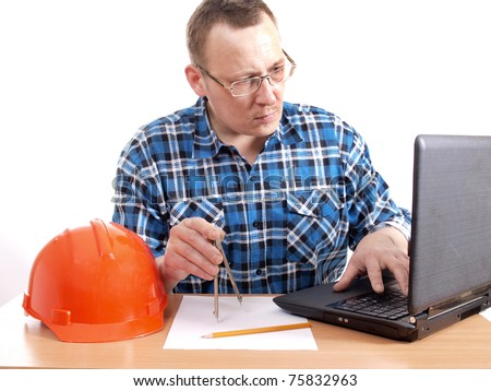 Color photograph of construction engineer in helmet with a computer - stock photo