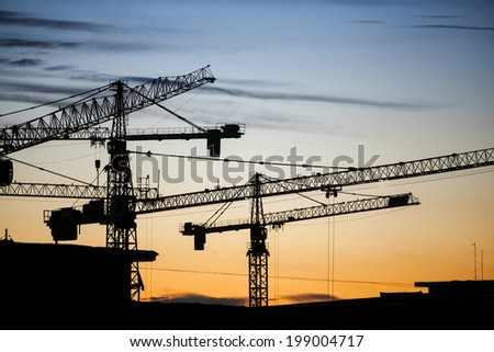 Color picture of some cranes on a construction site, as dusk. - stock photo