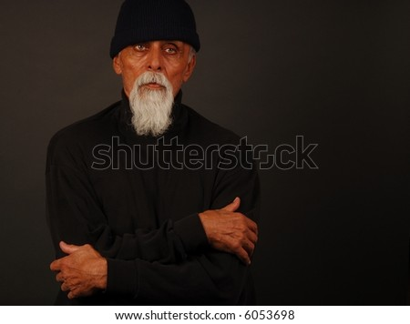 color portrait elderly male with white beard, sitting, arms folded, wearing black watch cap and black turtle neck looking right with copy space on right side of frame - stock photo