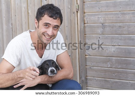Color portrait of young man about thirty-five years old, looking and smiling to the camera with his dog. - stock photo