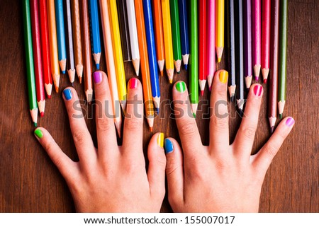 Color rainbow pencils and teenager's hands with multicoloured nails - stock photo