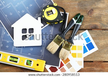 Color samples, decorative house, gloves and paintbrushes on wooden table background - stock photo