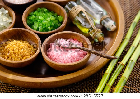 color sea salt in wooden bowl with bamboo grove ,massage oil on mat - stock photo