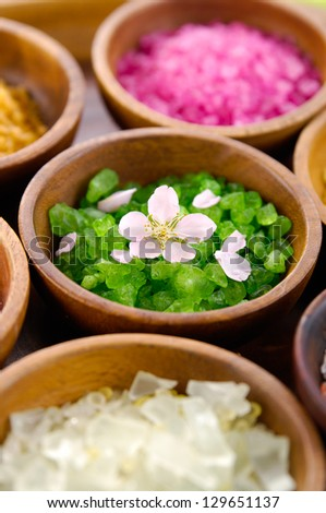 color sea salt in wooden bowl with spring flower and petals - stock photo