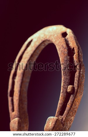 Color shot of a rusty horse shoe on a dark background. - stock photo