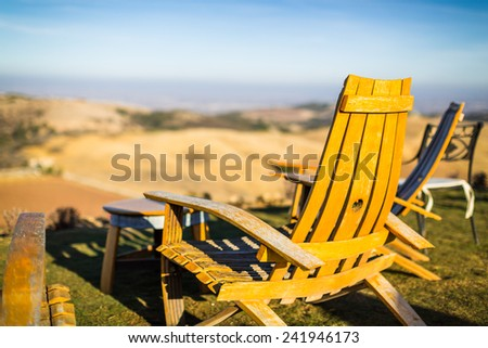 Color shot of adirondack chairs on green grass overlooking Paso Robles wine country at a winery in California - stock photo