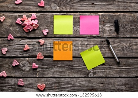 Color sticky note paper sheets with small hearts. Closeup on old wooden table. - stock photo