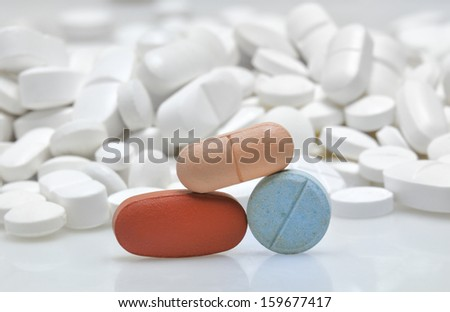 color tablets among white pills background - stock photo