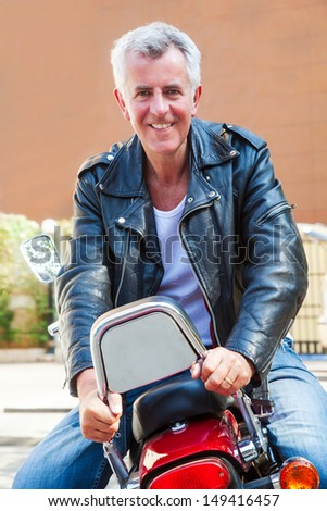 Color vertical portrait of a trendy fashion driven senior motor cyclist sat back to front on red cruiser smiling holding onto backrest. Generic shot location Bombay India with model release - stock photo