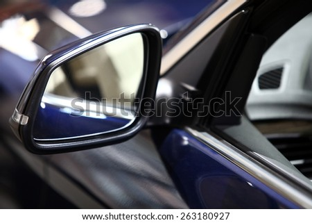 Color vertical shot of a blue car's side mirror. - stock photo