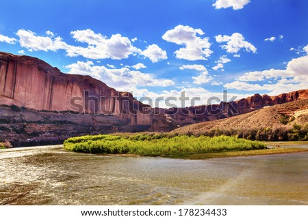 Colorado River Green Grass Red Rock Canyon Outside Arches National Park Moab Utah USA Southwest.  - stock photo