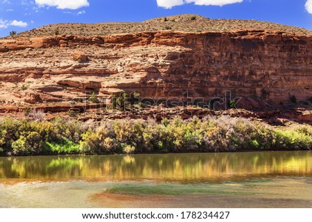 Colorado River Reflection Green Grass Red Rock Canyon Outside Arches National Park Moab Utah USA Southwest.  - stock photo