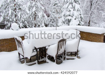 Colorado spring storm - unpredictable Rocky Mountain weather drops heavy snow in Denver, covering patio furniture in suburban back yard. - stock photo