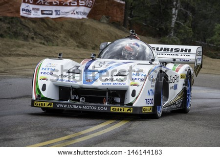 COLORADO SPRINGS, CO - JUNE 30: Nobuhiro Tajima #1 drives an E-Runner Pikes Peak Special to 1st place in Electric Class at the Pikes Peak International Hill Climb on June 30, 2013 in Colorado Springs. - stock photo