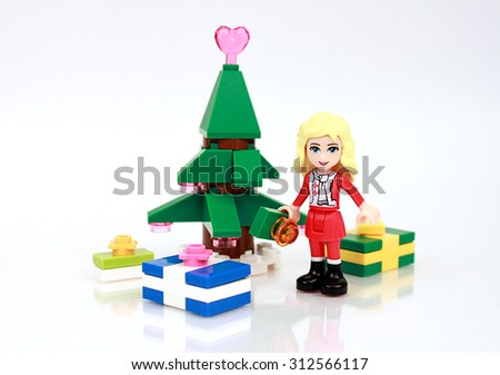 Colorado, USA - September 2, 2015: Studio shot of Lego minifigure Christmas girl in front of tree and presents. - stock photo
