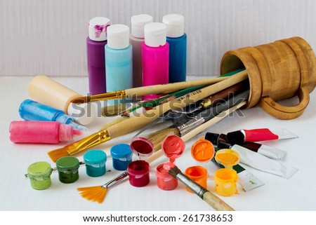 Colored acrylic paints and brushes in a wooden mug on a white background - stock photo