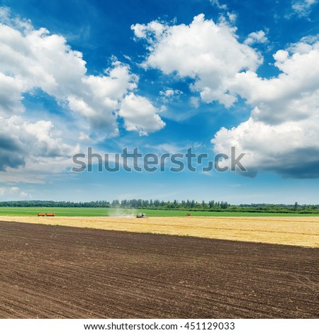 colored agriculture fields and clouds in blue sky - stock photo