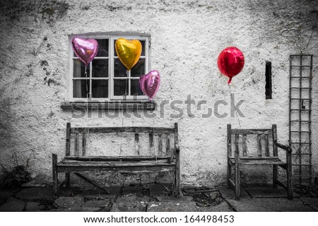 Colored balloons attached to old furniture in selective color image - stock photo