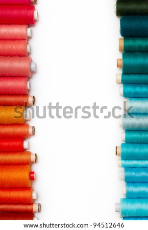 colored bobbins against white background. on the left red and orange bobbins and on the right blue and green - stock photo
