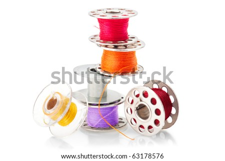 Colored bobbins for machine sewing isolated on white background - stock photo