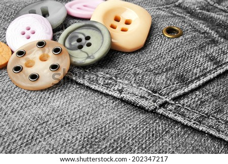 Colored buttons on a black denim - stock photo