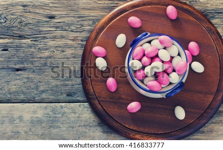 Colored candies covered with glaze on a round board on wooden background. Holidays and events. Sweet table. Space for text. Toned image. Top view - stock photo