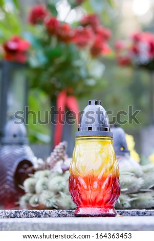 Colored candle on the grave  in a cemetery - stock photo