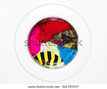 Colored clothes in washing machine window - stock photo