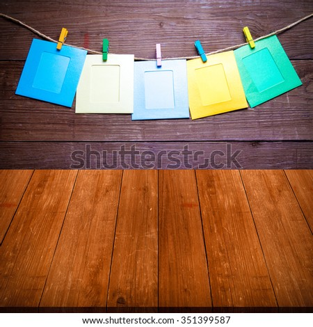 Colored clothespins with photo frames on rope on a wooden wall over old dark wooden table or board. New year theme. Collage. Space for text. Toned. - stock photo