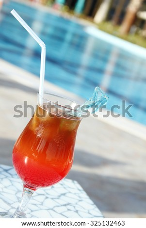 Colored cocktails Drinks Poolside. Turquoise water and a glass with a cocktail - stock photo