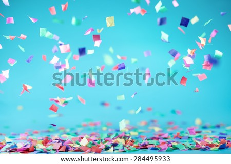 Colored confetti flying on blue background - stock photo