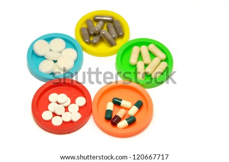 colored containers with different pills and capsules on white background - stock photo