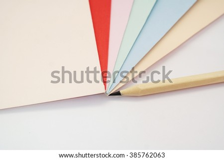 Colored drawing papers in a variety of colors in white isolated background with pencil - stock photo